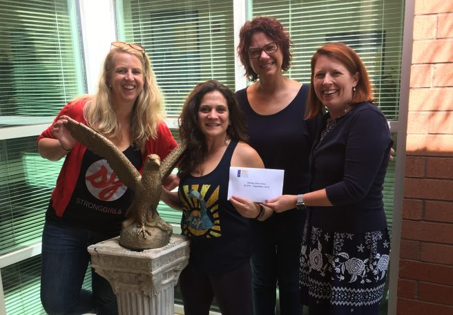 Strong Girls Serve Co-Founders receive checks from 100+ Women Who Care Athens member, Kim Klonowski, and founder, Sherry Clouser